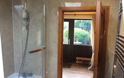 Bath and Shower showing heated towel rail with view towards main cottage door