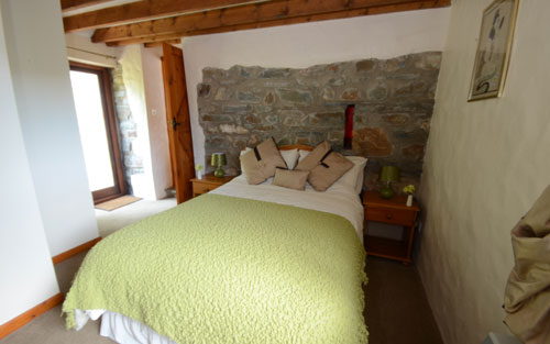 Master bedroom showing rear garden door at old chapel cottage self catering accommodation