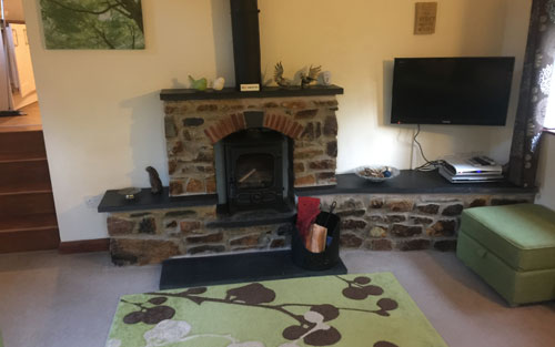 Keepers Nook cottage accommodation wood burning stove and showing the steps down from the kitchen into the lounge are